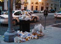 A trash can overflows with empty coffee cups after the parade.